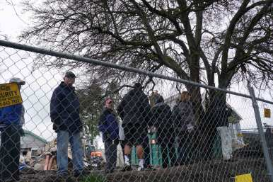 Members of the Bangasser family look on from behind the newly erected fence