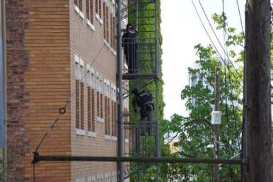SWAT assessing the suspect's apartment unit from the fire escape above E Howell
