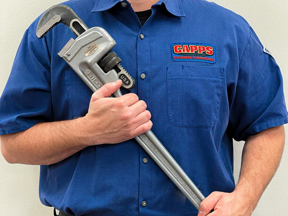 Capps plumber holding a pipe wrench