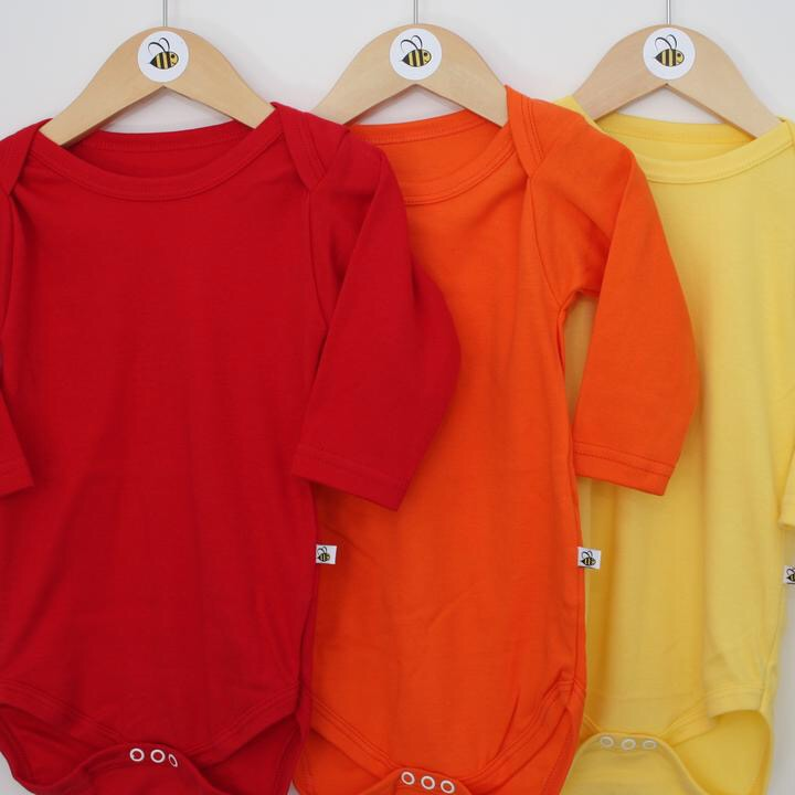 Set of baby vests from Beeboobuzz hanging on wooden hangers red, orange, yellow