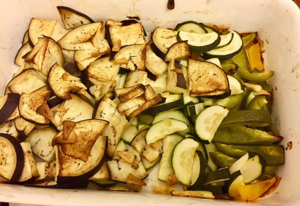 Slice the aubergine, courgette and peppers (and the onlions too) and on 175C roast them in the oven (in a roasting dish) for 25 -30 minutes. Add a little bit of olive oil.
