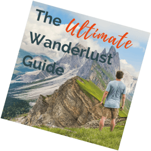 Image of man in blue shirt in the Swiss Alps admiring enormous mountains In the background with text overlay, The Ultimate Wanderlust Guide.