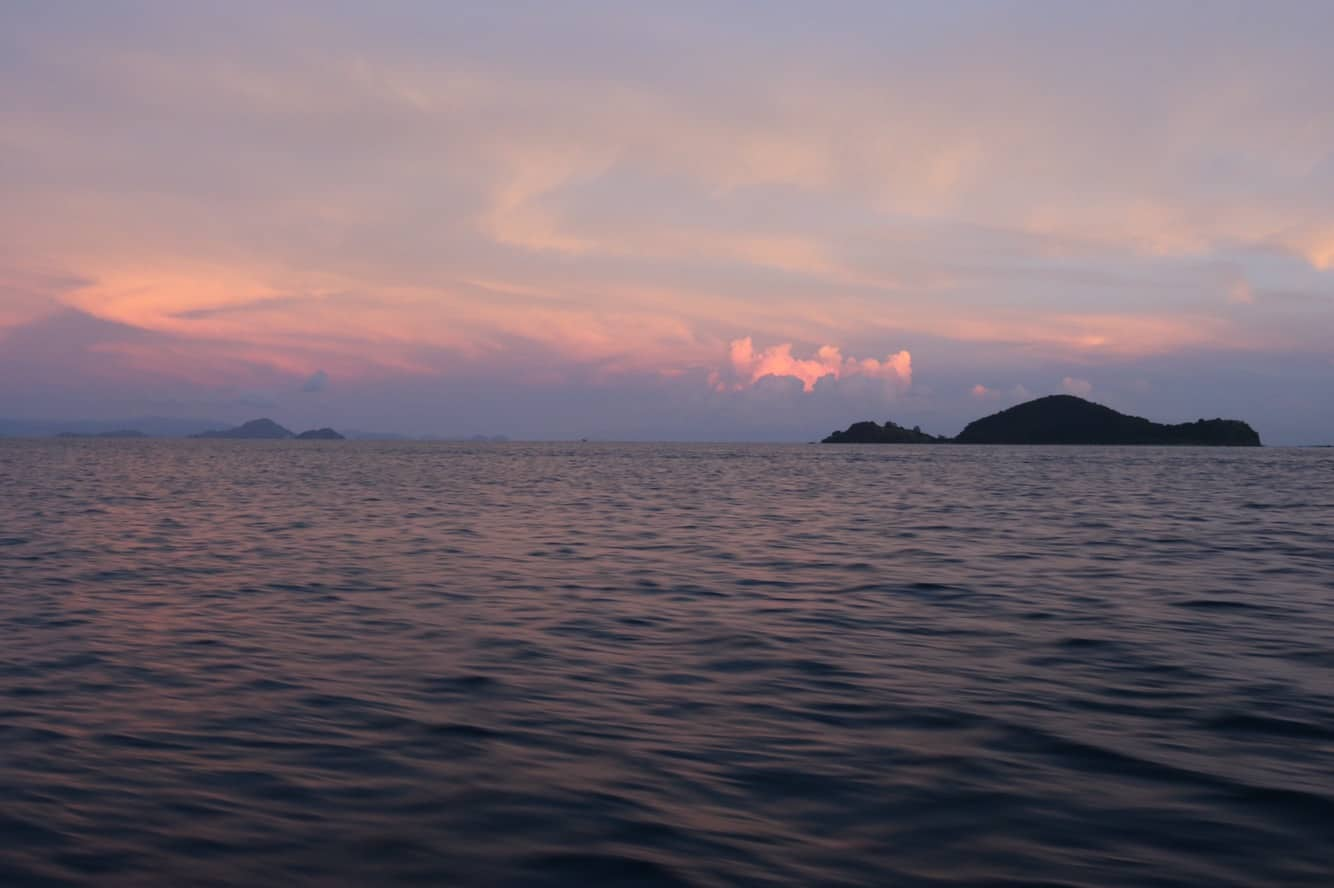 Ocean with a pink sky and a tiny island in the distance