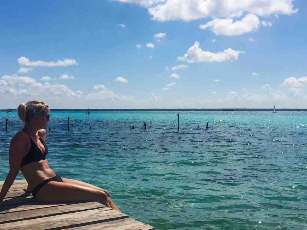 Girl sitting on a dock with a view over a blue lagoon