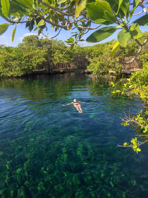 Girl laying in the water in a cenote in Tulum with lots af green