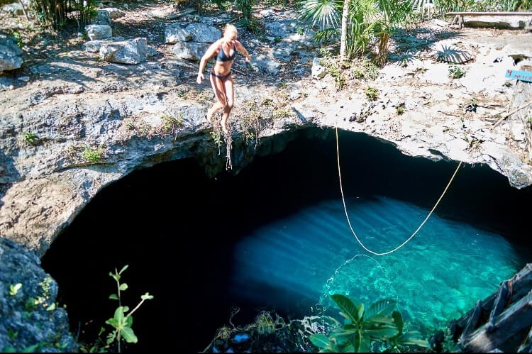 Girl jumping in cenote calavera in Tulum