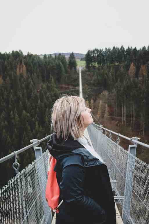 Side portrait of a girl looking up, but with her eyes closed standing on a long suspension bridge