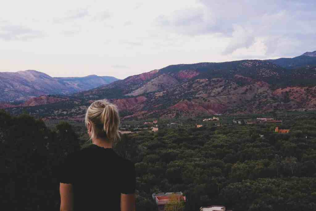 Girl with blonde ponytail overlooking mountains