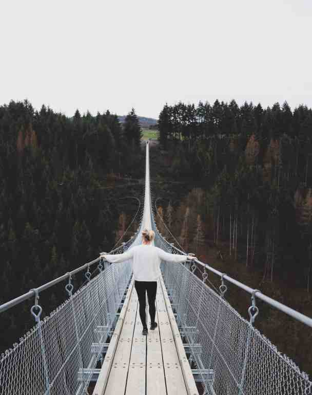 Girl with white sweater crossing a long bridge surrounded with pine trees