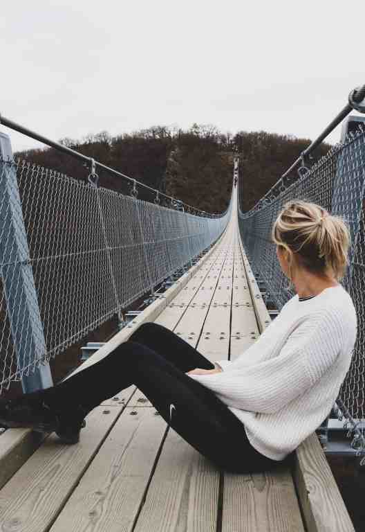 Blonde girl sitting down on a suspension bridge and looking at the other side of the bridge