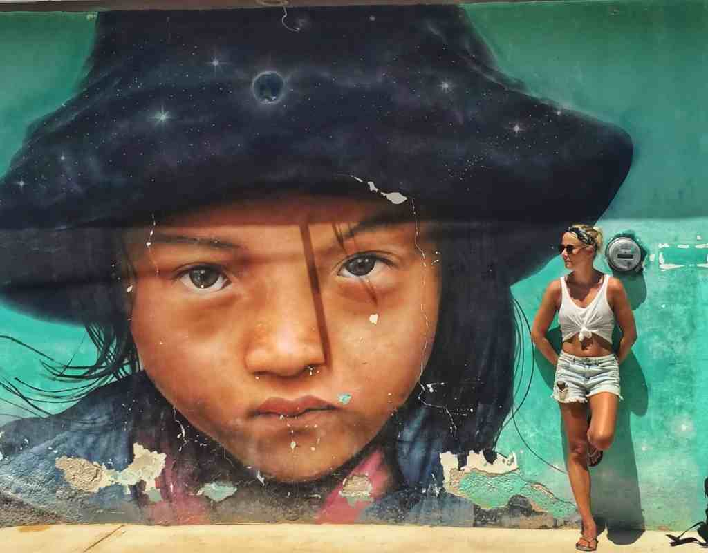 Girl next to a huge street art graffiti painting of the head of a mexican girl