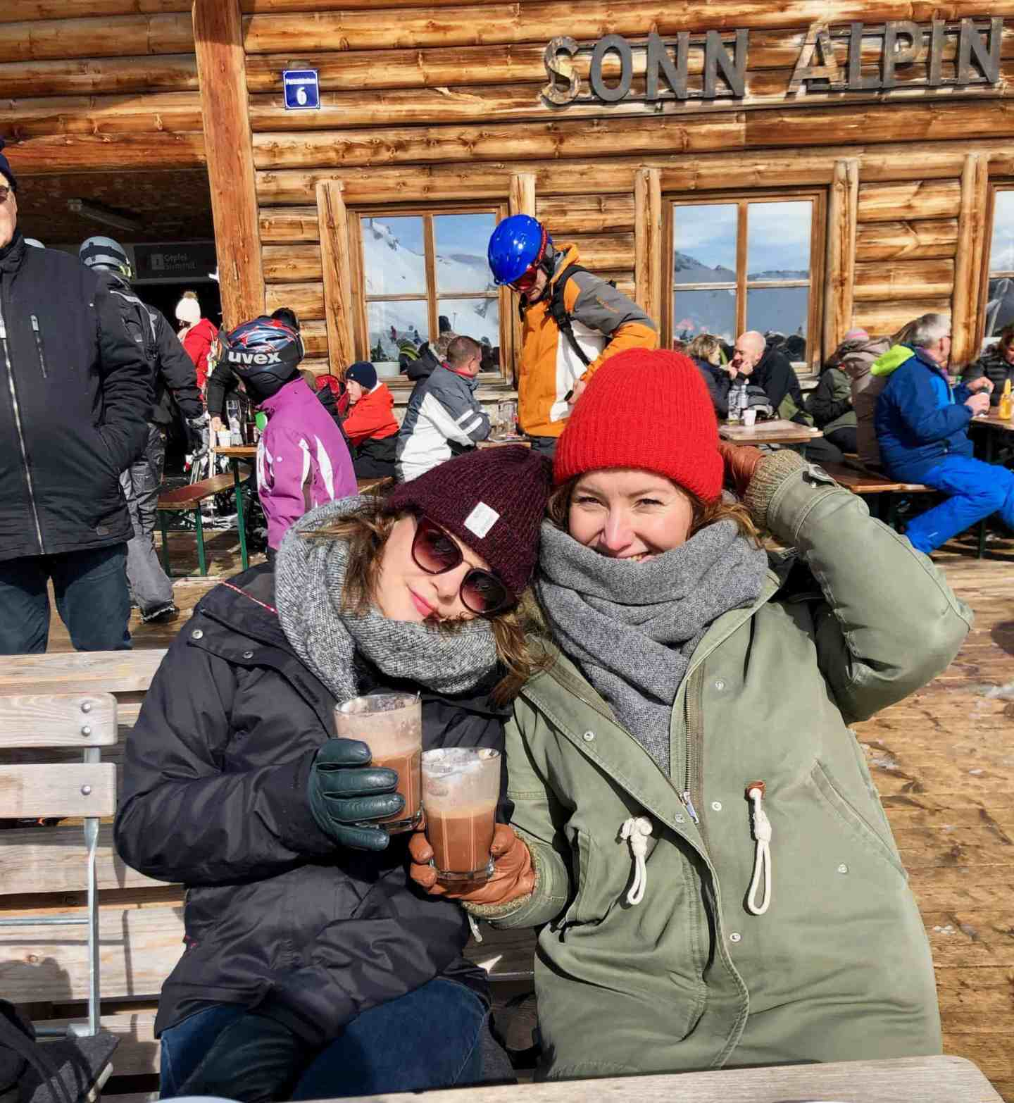 two girls with jackets on and hot chocolates
