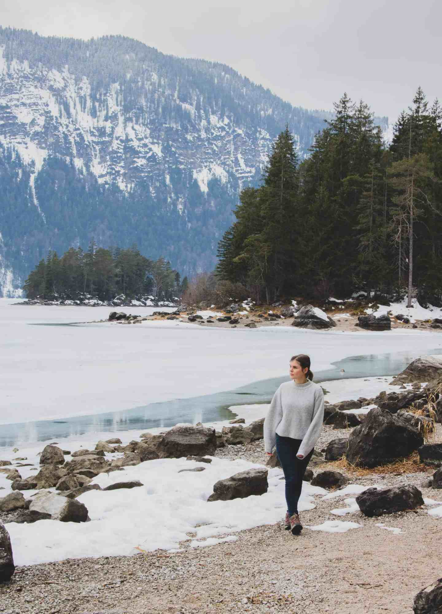 Girl walking next to a frozen lake with a mountain and pine trees behind