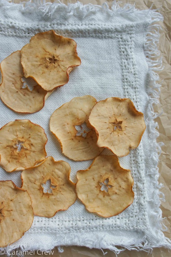 Homemade apple chips glazed with maple syrup, served with thick, buttery caramel dipping sauce - a delicious, easy recipe for a sweet snack.