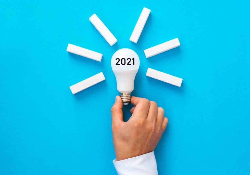 Businessman holding bulb with 2021 inspiration ideas and goals. Business solution and development concept