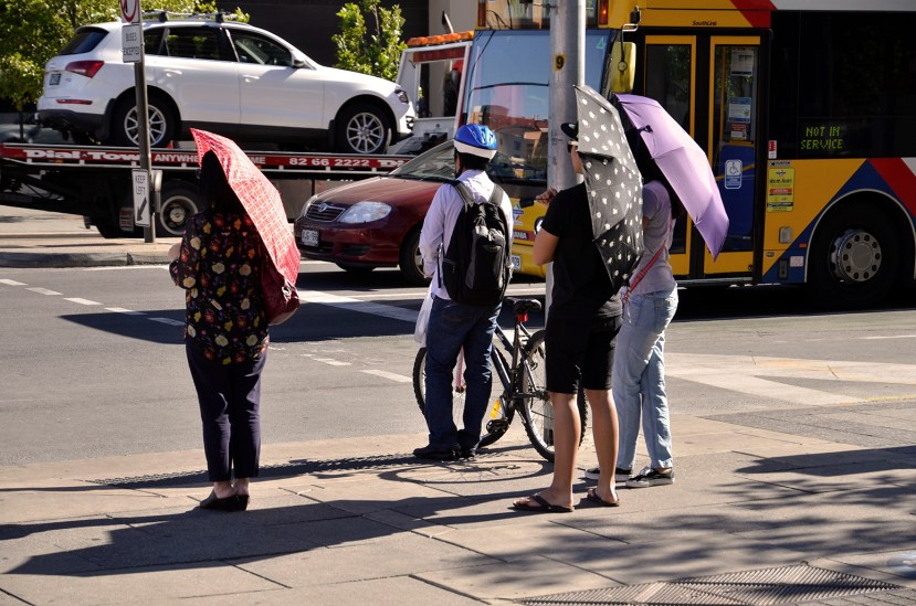 DN62FD Adelaide, South Australia 19th December 2013. Commuters in King William Street, Adelaide shelter from the heat in the grip of a 43c heat wave, with the city suffering its hottest December day since 1931. Credit: CandyAppleRed Images/Alamy Live News