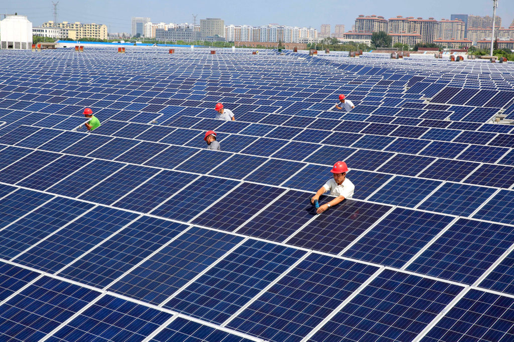 Workers install solar panels on the rooftop of a textile factory in Nantong, China. Credit: Imaginechina Limited / Alamy Stock Photo. W83K69
