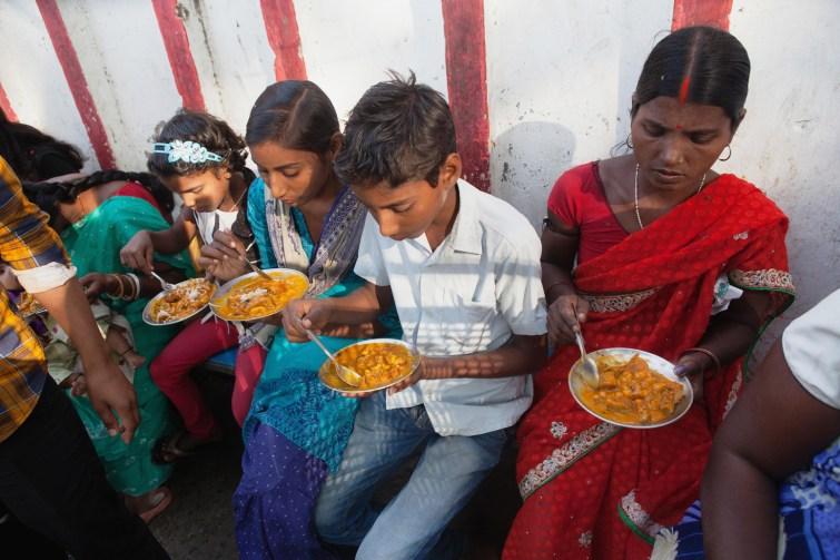 A family eating vegetarian street food in Bodh Gaya, India.