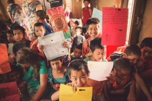 Children from a Nepali orphanage hold up letters delivered by Letters in Motion, June 2015.