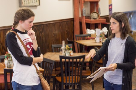 Esther Lewoczko, freshman music performance major, receives instruction from Jessica Johnson, volunteer coordinator for the ComeUnity Cafe. | Photo by David Parks, staff photographer