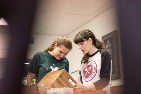 Hannah Johnson, sophomore business administration major, and Anna Guthrie, sophomore art studio major, collaborate in helping organize the ComeUnity Cafe. | Photo by David Parks, staff photographer