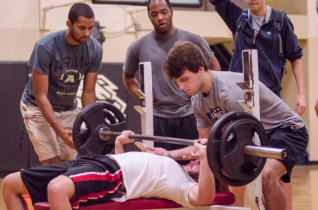 With the spotting of his Alpha Tau Omega brothers, Dallas Abraham, sophomore chemistry major, pushes through his final reps in the bench press challenge during the Union's Fittest Team competition. | Photo by David Parks, staff photographer