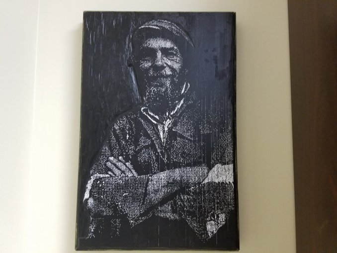 A portrait in a block of wood which was carved by Steve Halla and covered with ink.