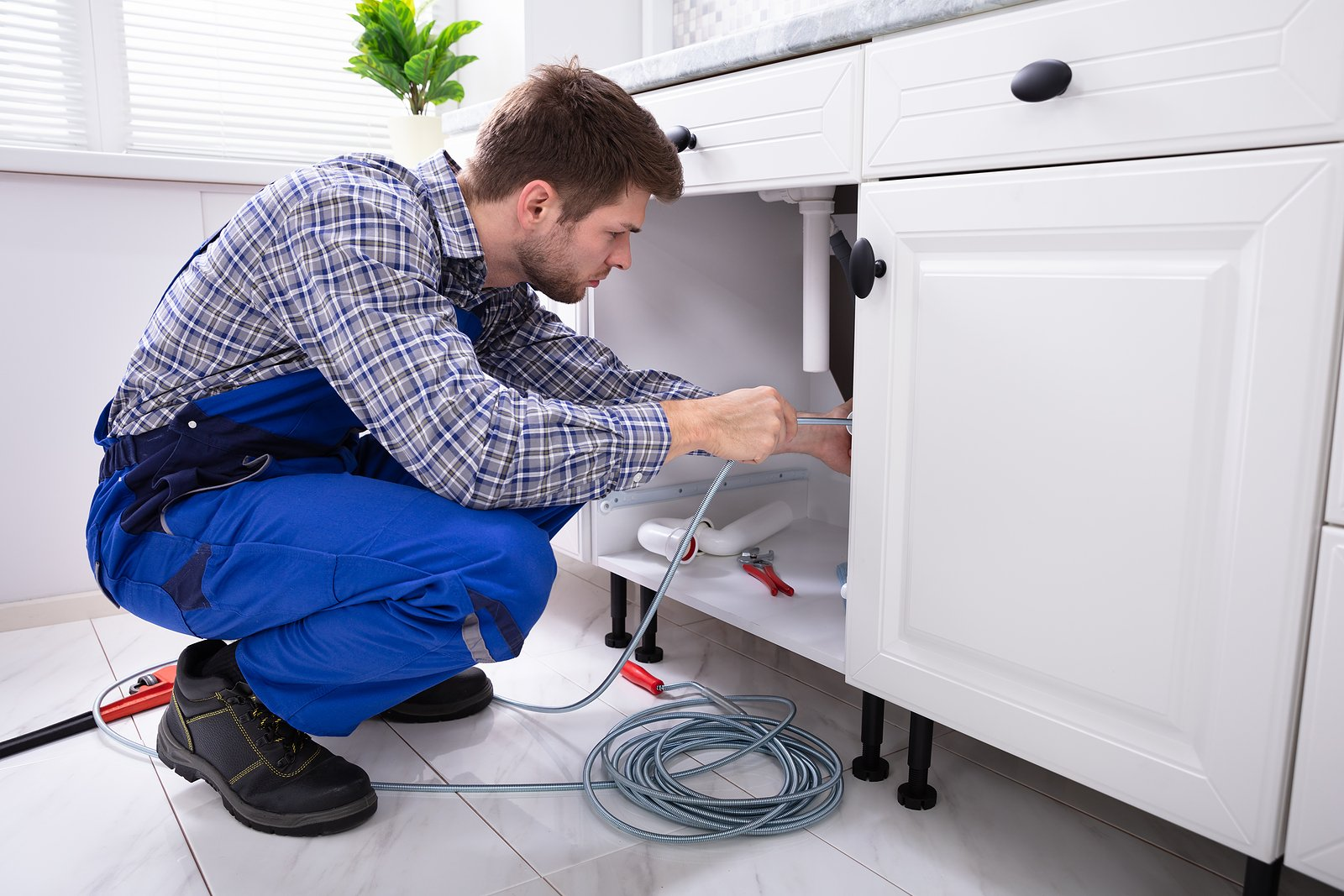 Young-Male-Plumber-Cleaning-Clogged-Sink-Pipe-in-Kitche