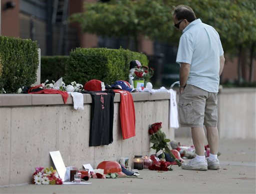 Henry Simpson looks over mementos placed at a makeshift memorial to St. Louis Cardinals' Oscar Taveras outside Busch Stadium Monday, Oct. 27, 2014, in St. Louis. Taveras, the Cardinals' outfielder regarded as one of the majors' top prospects, died Sunday in a car accident in his native Dominican Republic. He was 22. (AP Photo/Jeff Roberson)