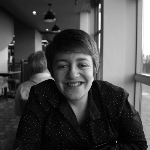 Image of Amy Hassett. Black and white photo wherein Amy is smiling at the camera wearing a shirt with dots on it and is sitting at a table in a restaraunt