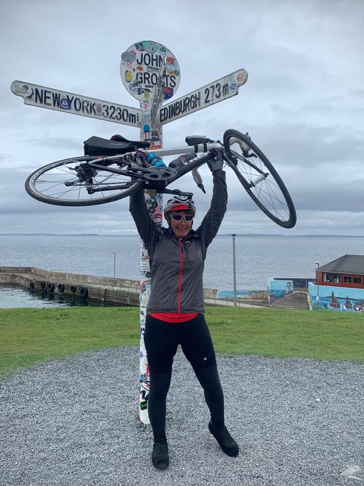 Jacky Massos holding her bike above her head at John O'Groats