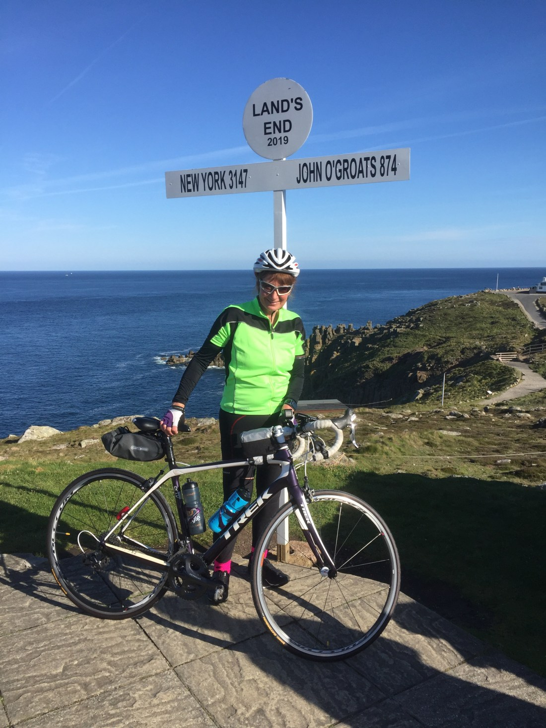 Jacky on her bike at Lands End on her way to John O'Groats