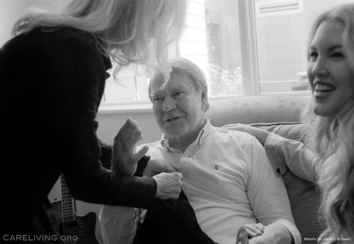 Kim and Ashley Campbell help Glen Campbell dress for the day. Photo by Marty Stuart for CareLiving.org