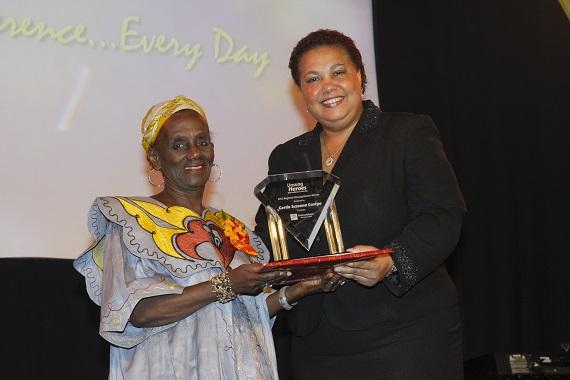 Gerda Gosepa. Caption: Regional Unsung Hero 2012, Gerda Gosepa (left) proudly and happily collects her award from Managing Director, HR, CIBC FirstCaribbean, Ella Hoyos.