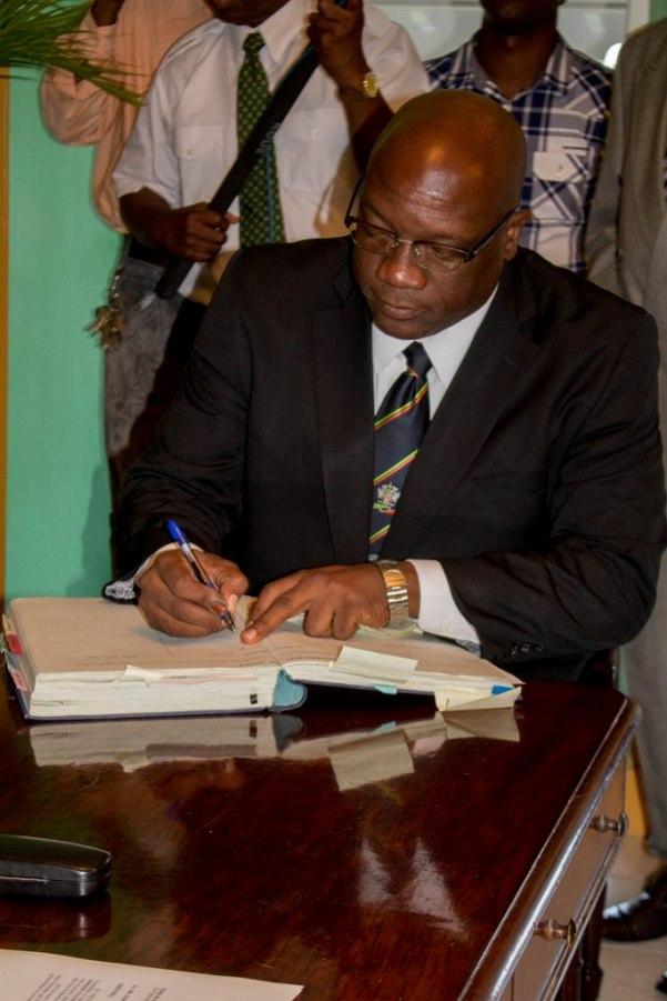 Honourable Dr. Timothy Harris signs documents. Photo courtesy ZIZ