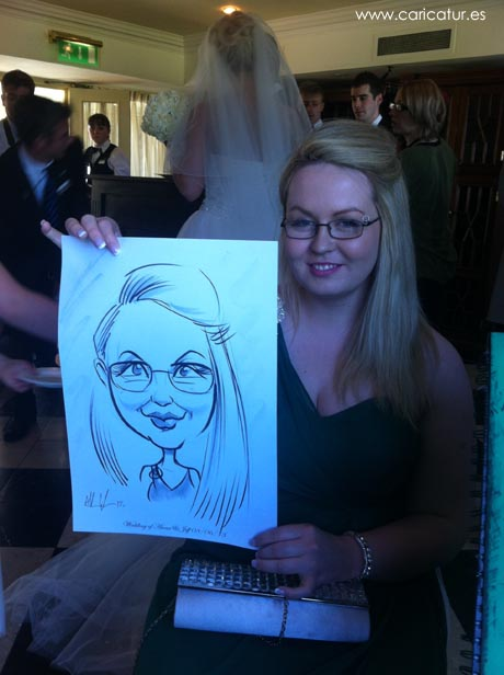 A young woman smiling with a caricature by Allan Cavanagh of Caricatures Ireland.