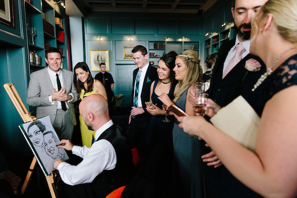 Wedding guests look on laughing as Caricature Artist Allan Cavanagh draws his hilarious fast caricatures