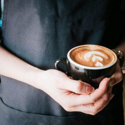 Hände halten eine Kaffeetasse.