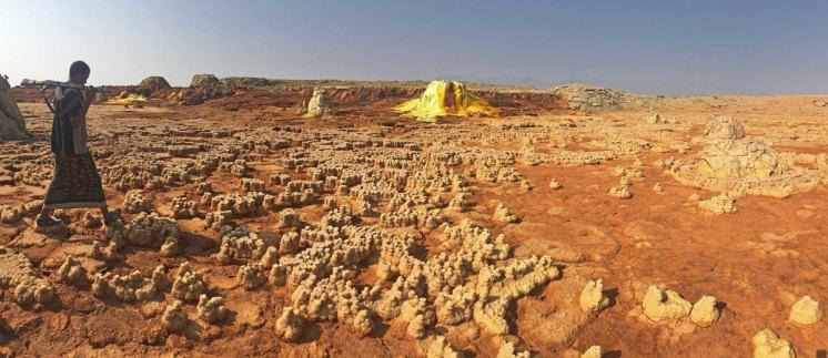Lagunas desecadas con restos ferruginosos, y al fondo una montaña de azufre amarillo