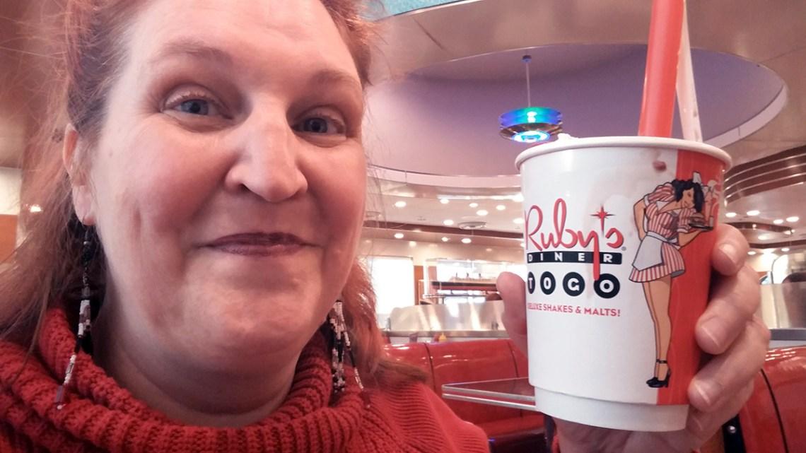 Carma holding a small Ruby's dark chocolate raspberry milkshake