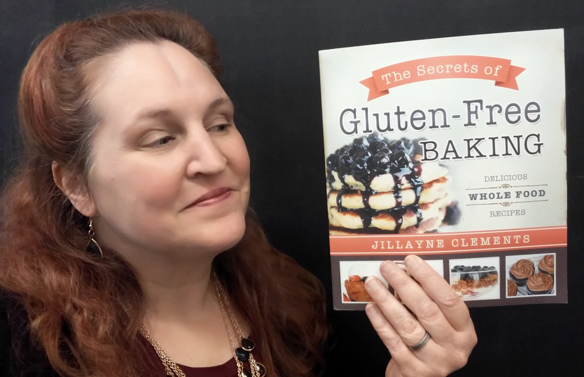 Carma Spence holding a copy of The Secrets of Gluten-Free Baking by Jillayne Clements