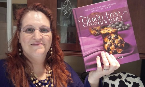 Carma holding a copy of Gluten-Free Goes Gourmet