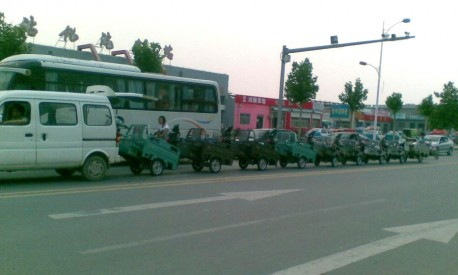 Transporting nine motorized tricycles, the Chinese Way