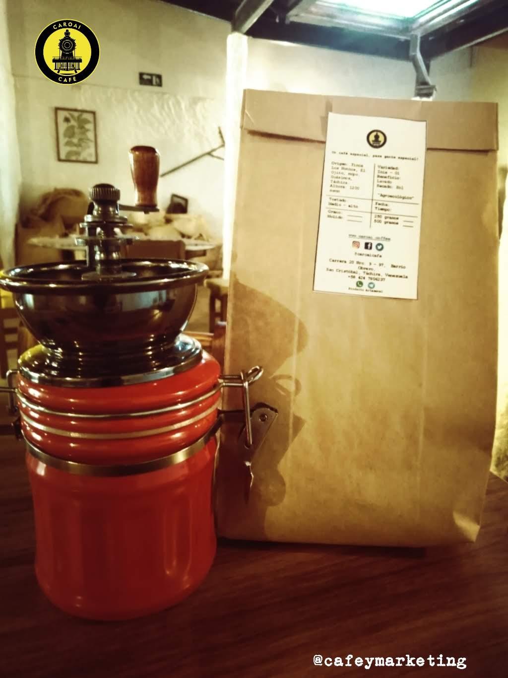 Molino de café manual, casero con una presentación de café tostado de Caroai Café