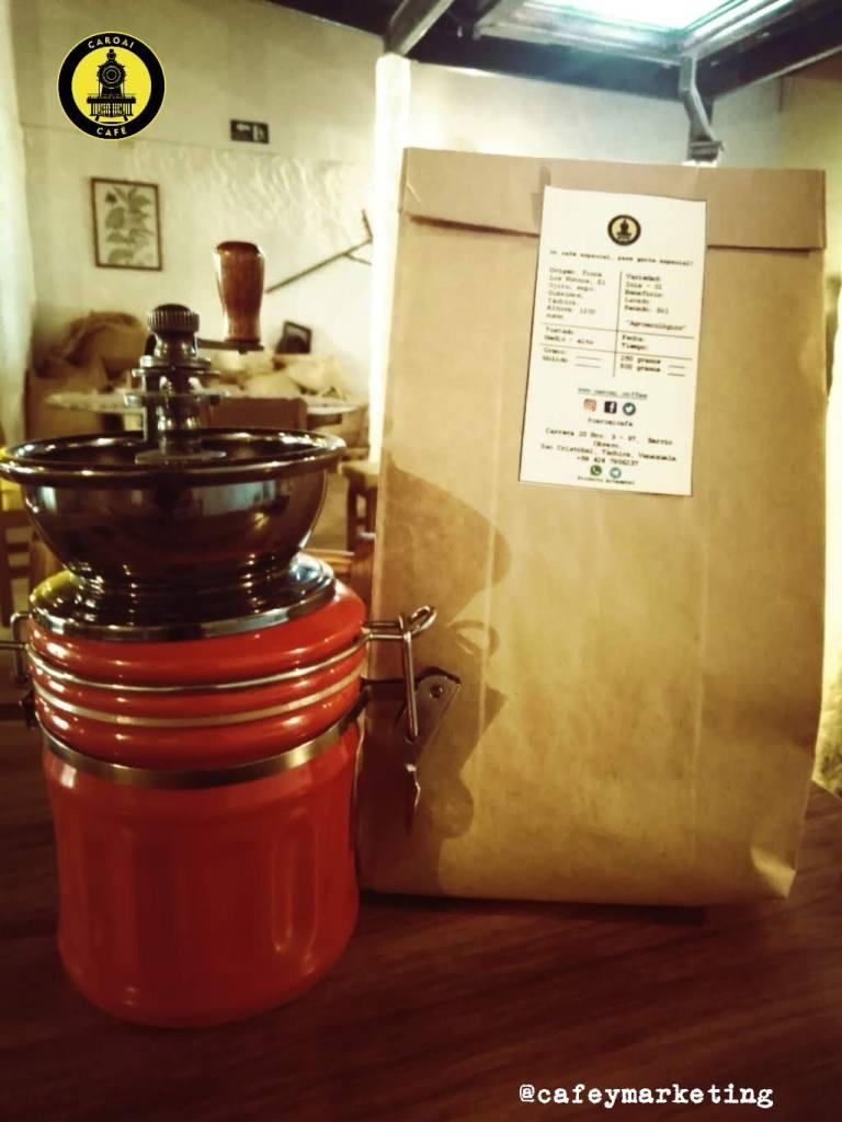 Molino de café casero con una presentación de café tostado de Caroai Café