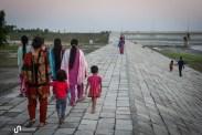Familien spazieren auf dem Damm.