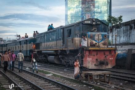 Kinder spielen während ein Zug an ihnen vorbeirattert.