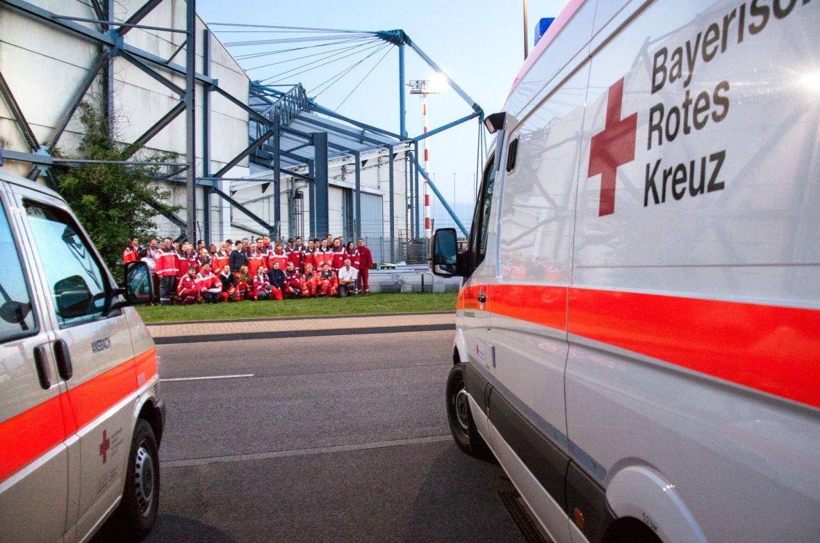 Teamfoto Deutsches Rotes Kreuz zwischen Krankenwagen