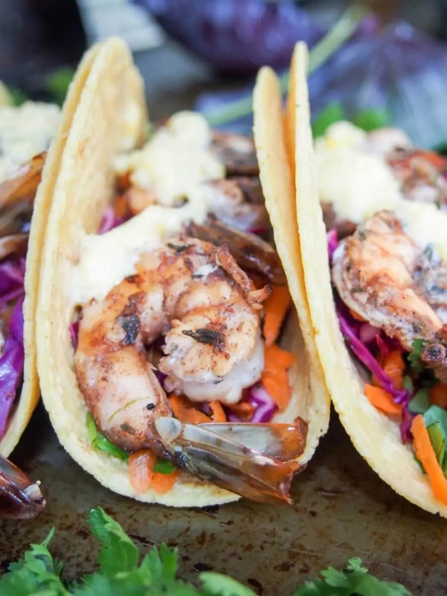 Spice marinated shrimp, a crunchy slaw and a sweet and creamy mango crema to top it all off - these jerk spiced shrimp tacos are so good (& easy too).