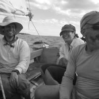 three smiling people in a sailboat